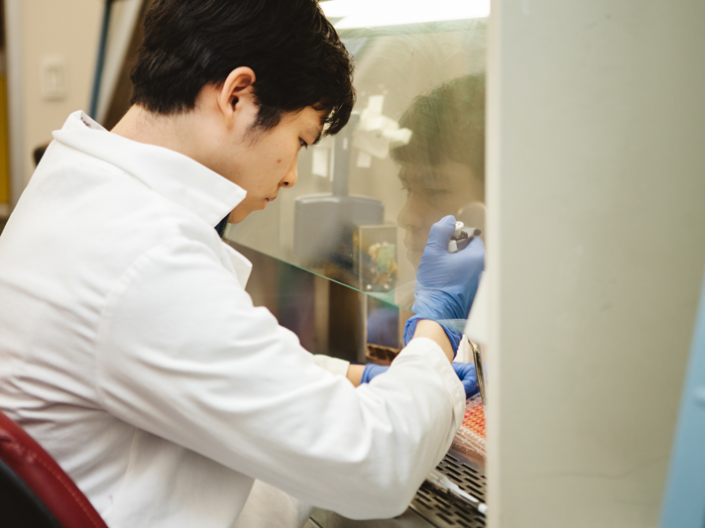 Man in white coat working with a pipette under a clear laboratory fume hood