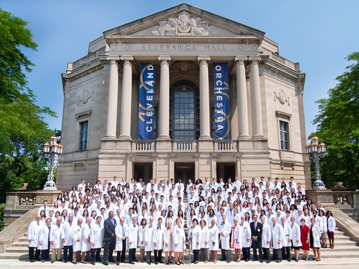 Large group of medical students in white coats standing in front of Cleveland's Severance Hall