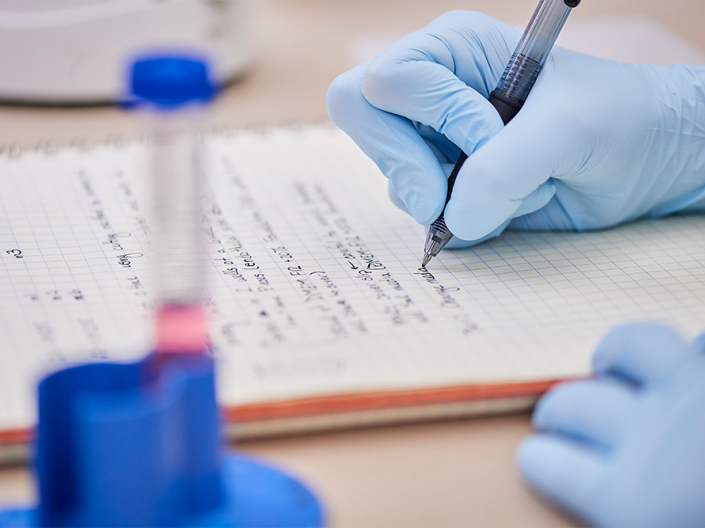 Researcher writing notes with blue sterile gloves on