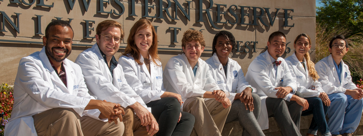Eight MSTP students in white coats sitting in front of Case Western Reserve University sign