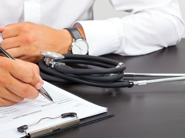 A doctor filling out paperwork with a stethoscope beside them