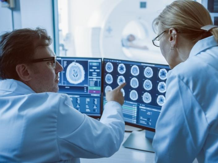 Two scientists in lab coats looking at brain scans