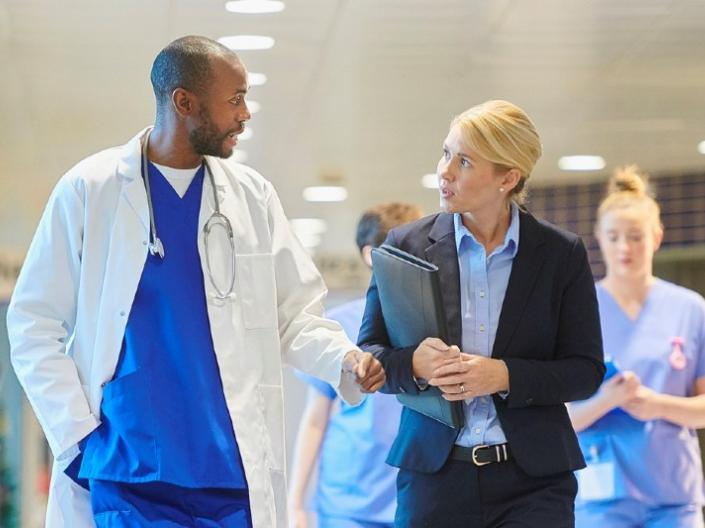 Two doctors talking while walking through a hallway