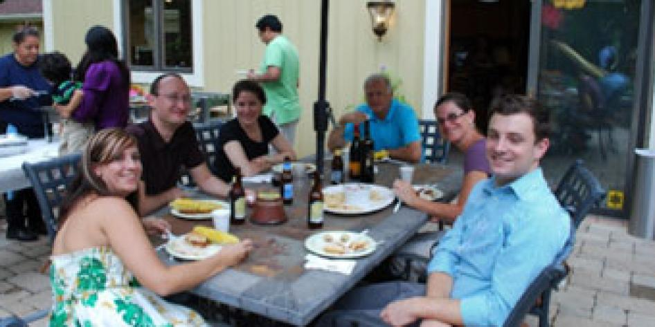 Annual vascular picnic, 2012 with six people having lunch outdoors around a table, with a serving table with three people in the background