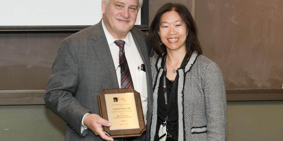 Photo of George H. Meier with Virginia Wong after giving his Beck Lecture in Vascular Surgery talk. Dr. Meier is holding a plaque.