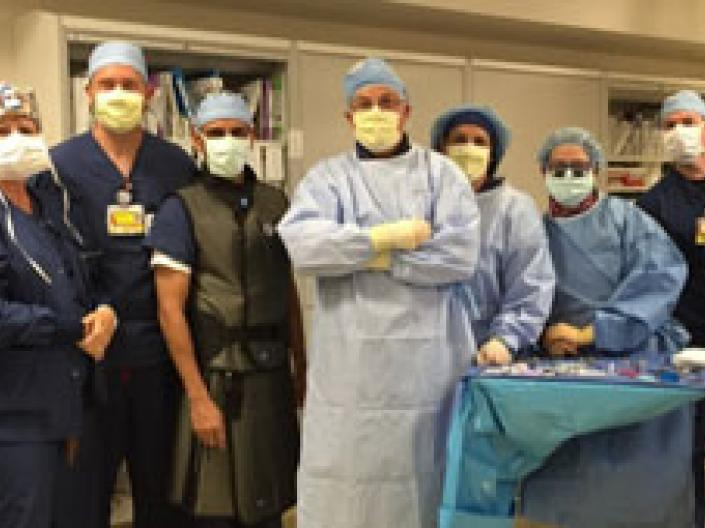 nine surgeons standing in OR theater in dark and light blue gowns