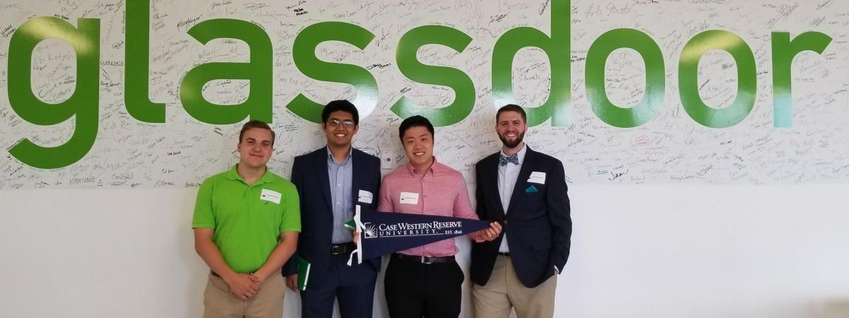 students dressed business casual  in front of a glassdoor logo