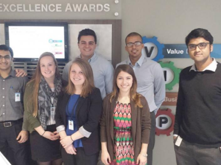 CWRU MEM students posing in front of a sign that says Excellence Awards
