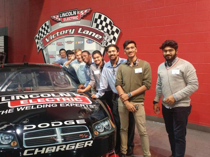 MEM students posing with a racecar at Lincoln Electric