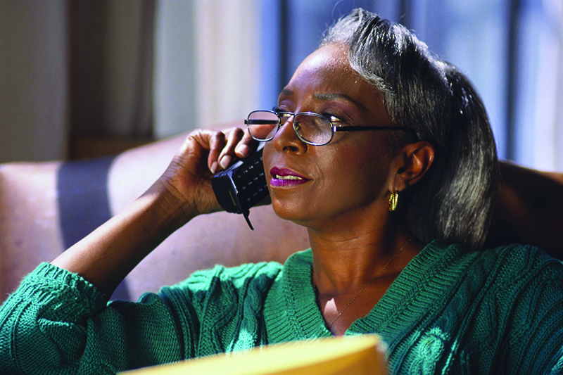 A women using the phone talking to a distance caregiver
