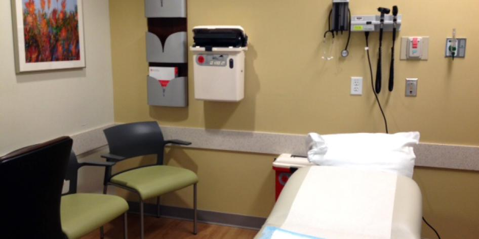 The exam room has two chairs and then a medical bed for the patient.