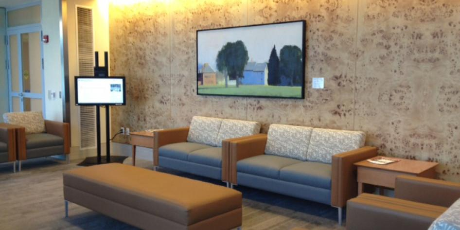 The waiting room has a monitor and couches for patients to sit