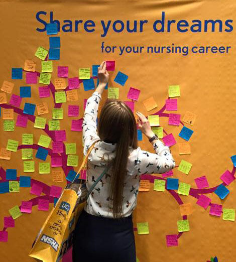 "Picture of a new FPB student adding her wishes to a ""share your dreams"" poster"