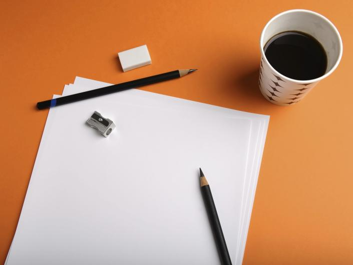 Stock image of a cup of coffee next to sheets of blank paper, two pencils, and a tiny pencil sharpener.
