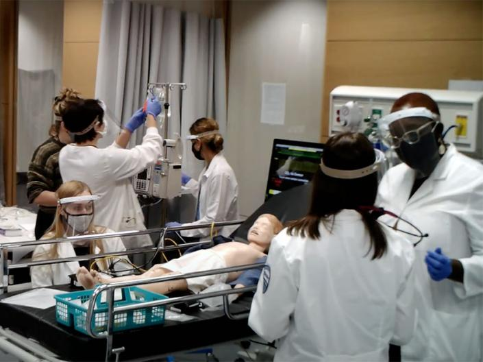 Nursing students wearing PPE work in a clinical lab class in fall 2020.