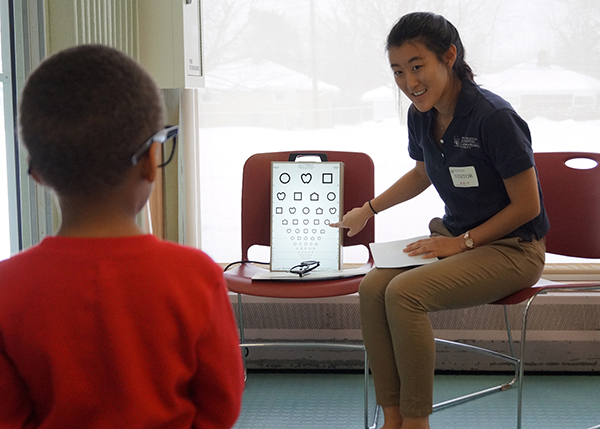 Photo of Nursing student giving an eye exam to a child.