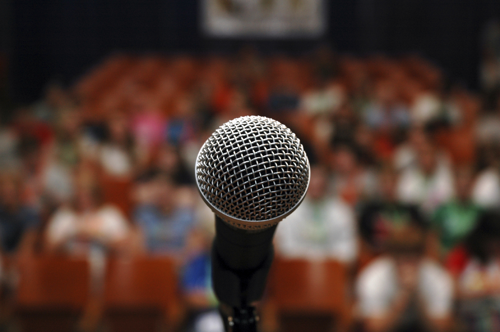 Stock image of a closeup on a microphone with an audience in the background.
