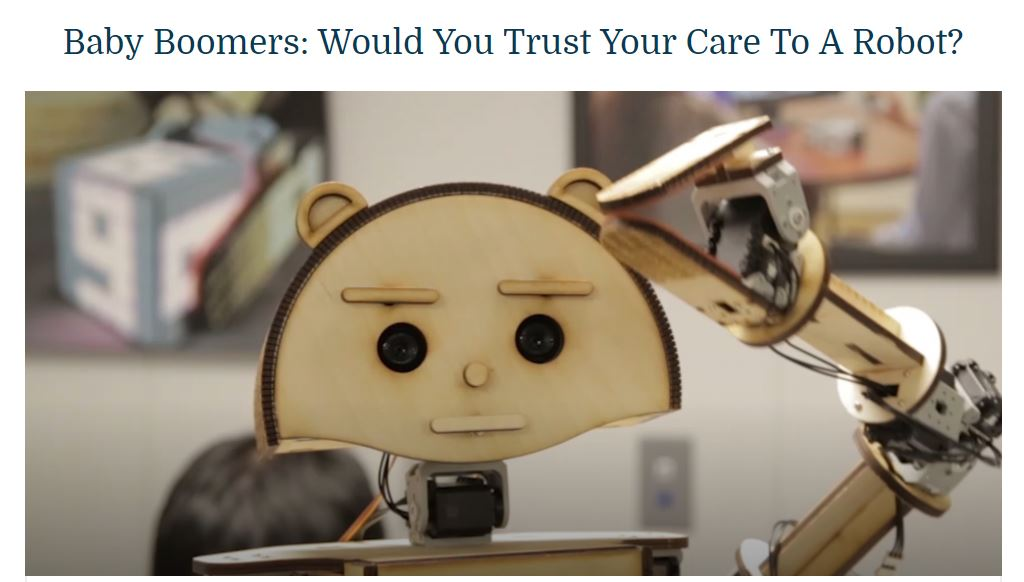 "A screenshot of an ideastream® video about the Smart LIving Lab's robot companion project by Case Western Reserve University nurse researchers. The headline of the story, visible at the top of the picture, reads: ""Baby Boomers: Would You Trust Your Care to a Robot?"" In the photo, a plywood-based robot named Woody is shown."