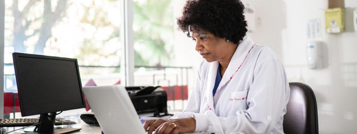 Woman wearing a white lab coat at a computer.