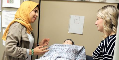 Picture of two women discussing techniques over a dummy patient.