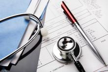 Picture of a stethoscope and pen laying across a file.