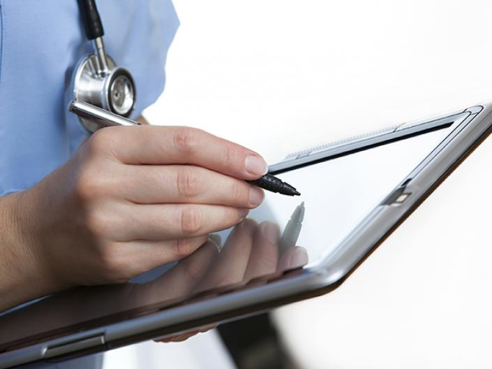 Stock photo of a doctor writing on a tablet.