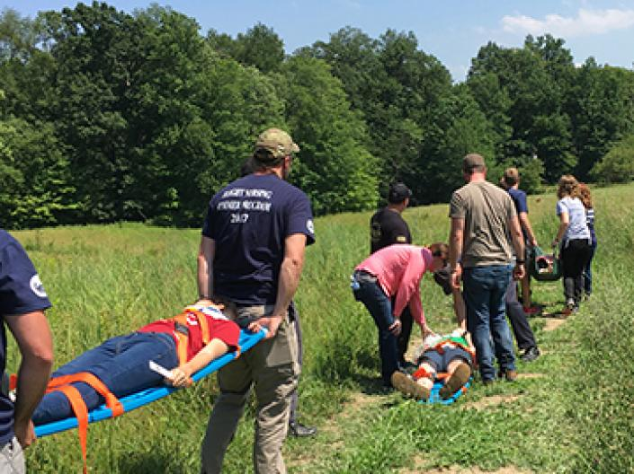 Picture of FPB flight nursing students carrying demo patients on stretchers across a field.