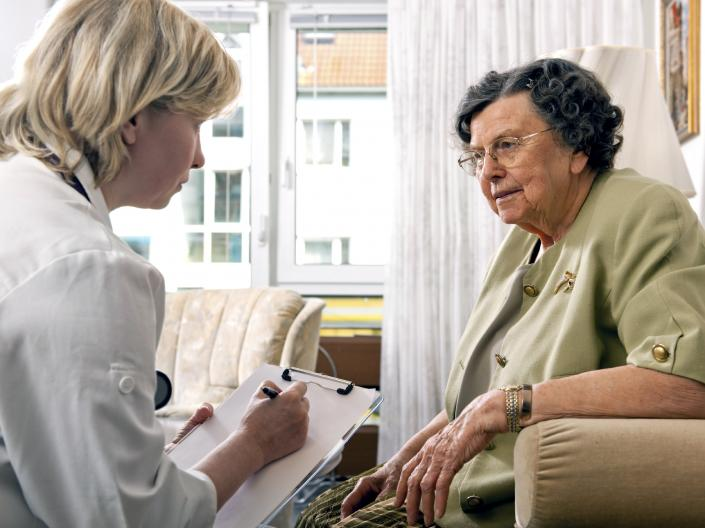 Female nurse asking questions to an elderly patient.