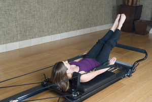 Woman using a pilates reformer machine
