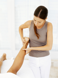 Massage therapist massaging a person's leg