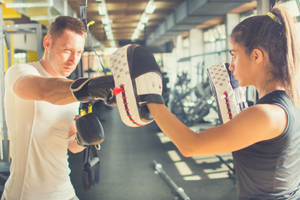 Man boxing hitting pads held by woman