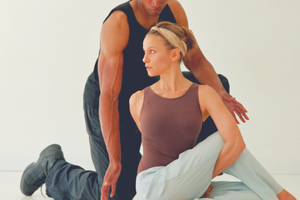 Male yoga instructor assisting woman in yoga pose on floor