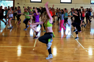 large group doing Zumba in gymnasium