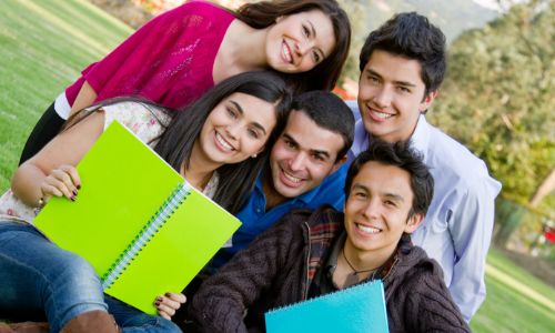 group of five college students outside with notebooks