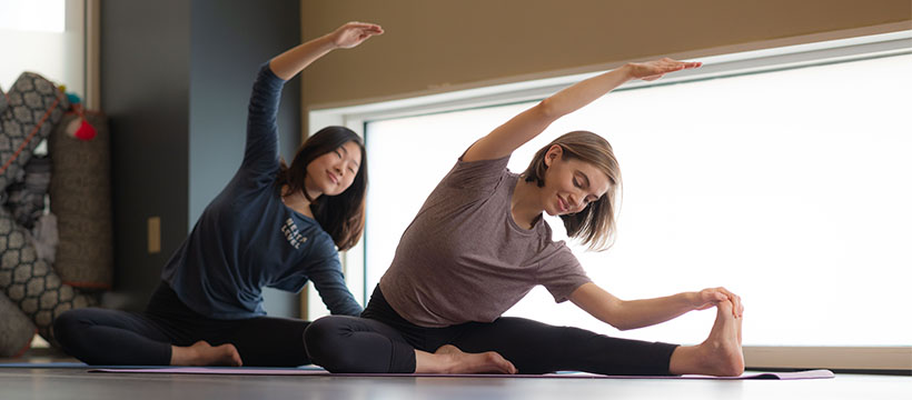 Two women in side stretch on floor of yoga studio
