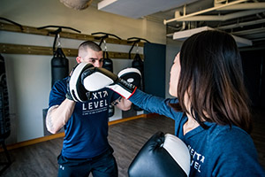 Next Level trainer boxing with client in open studio