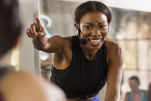 Woman cycle instructor pointing at class