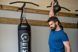 Man holding kettlebell overhead in front of a heavy bag