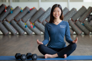 Woman in yoga pose sitting on floor with dumbbells