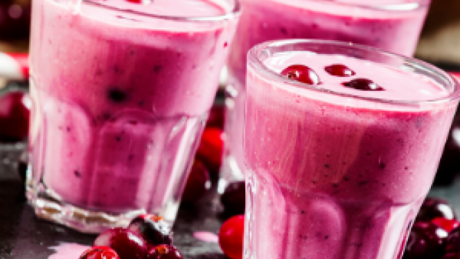 Three berry shakes with berries around them