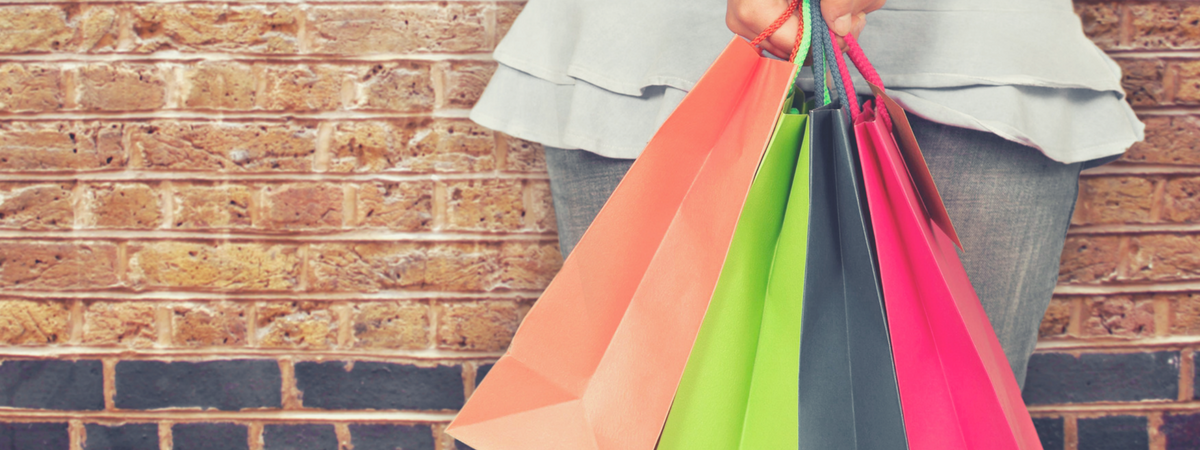 Woman leaning on brick wall holding different color shopping bags