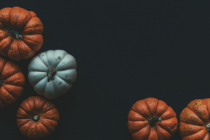 black background with small white and orange pumpkins