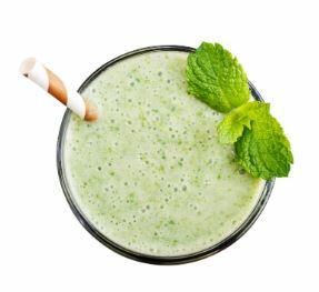 Green shake from the top with straw and mint leaves
