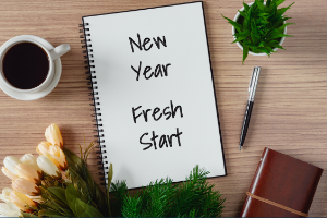 Planner on table with coffee and plants that says New Year Fresh Start