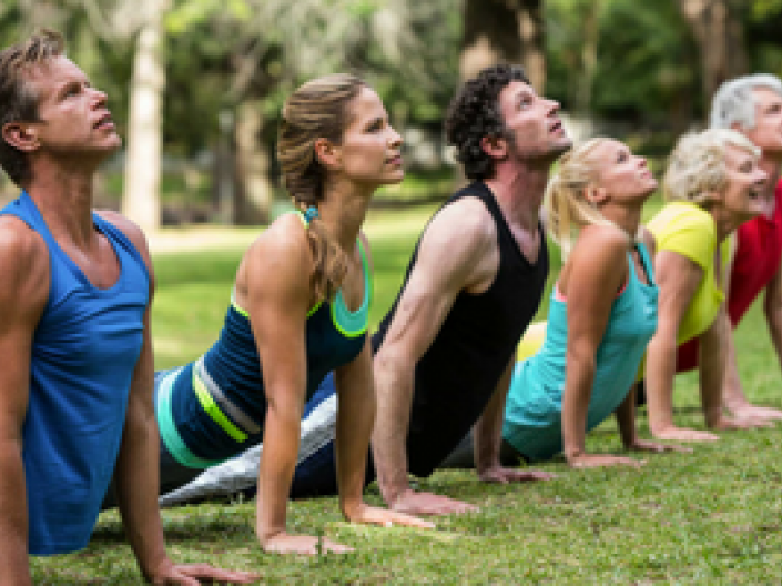 Group in line doing yoga on grass