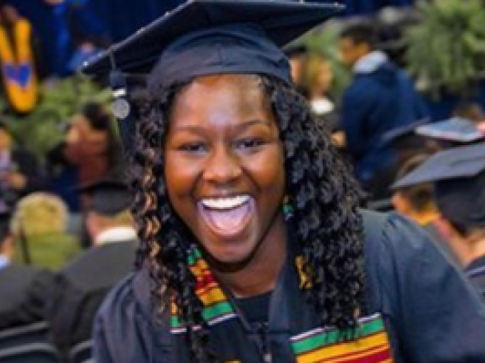 closeup of student smiling at graduation wearing black robes and cap