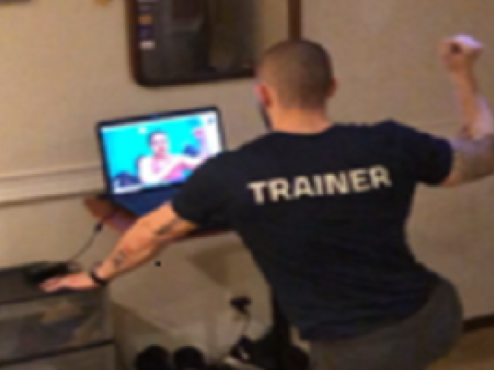 Man with trainer on the back of shirt looking at someone on computer screen