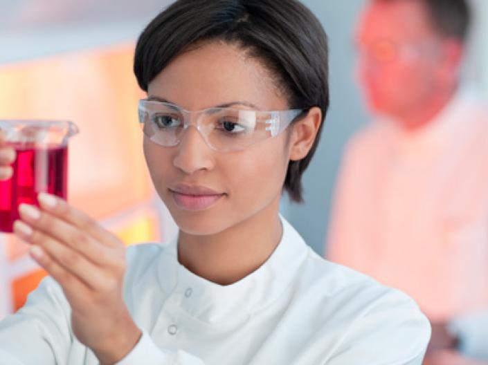 A woman examining a beaker wearing a lab coat and goggles