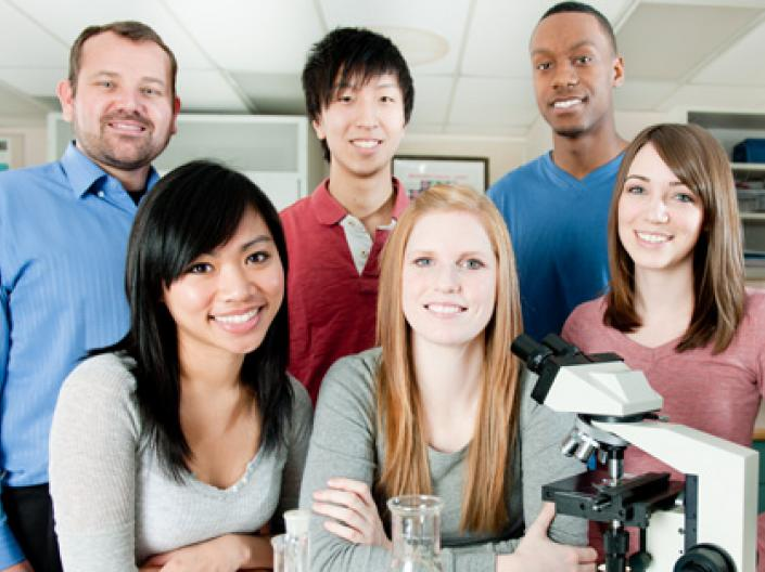 A group shot of 6 people in a lab standing behind a microscope