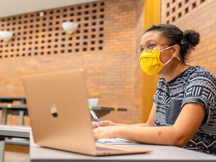 A student wearing a yellow mask sitting in classroom with a laptop.